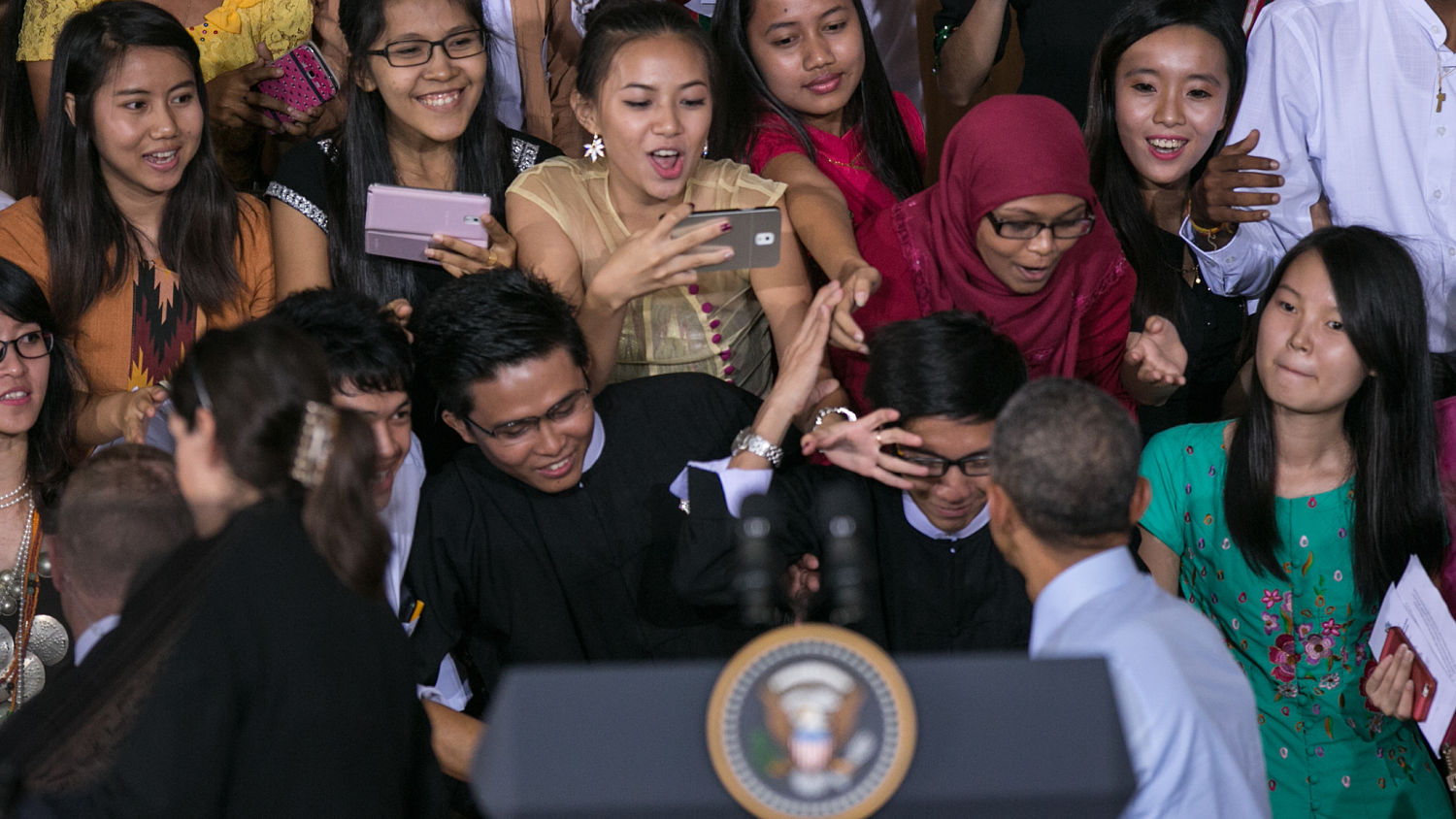 One woman lurched at Obama while photographing it at the same time.