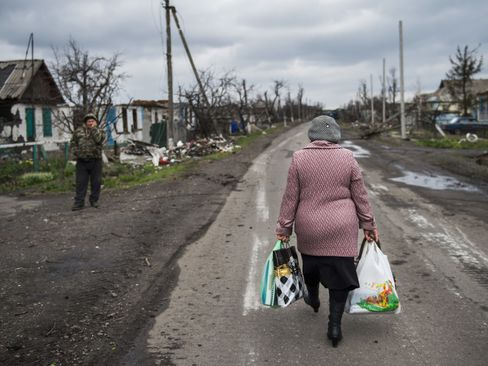 A woman carries walks back to the village of Nikishino in Ukraine, on April 21, 2015.