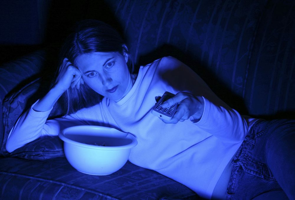 A woman watching TV late at night.