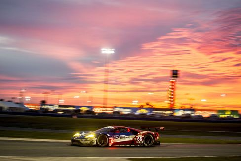 The No. 66 Ford GT of Joey Hand, Sebastien Bourdais, and Dirk Muller drives beneath the rising sun on the Daytona International Speedway.