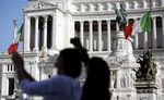 Tourists take photographs in front of a monument to the unknown soldier in Rome, Italy.