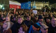 """People hold up a Polish and EU flag and copies of the Constitution as they gather in front of the presidential palace in Warsaw under the slogan """"Free courts, free elections, free Poland."""""""