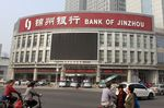 Pedestrians walk past a branch of Bank of Jinzhou in Tianjin city, China.