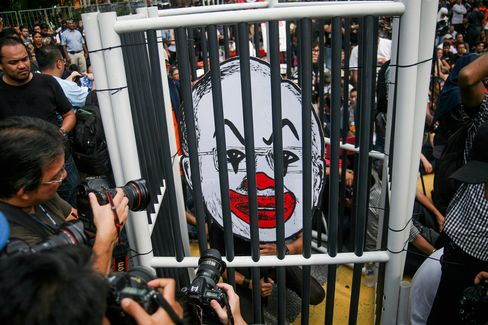 Malaysian activist with a caricature of Najib Razak's face on Aug. 27.