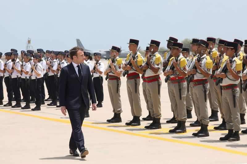 French president Emmanuel Macron reviews the troops as he visits the French military base in Djibouti on March 12