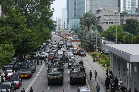 Armored police and military vehicles secure the explosion site.
