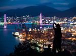 A woman uses a smartphone to take a photograph of the illuminated Port of Busan in Busan, South Korea.
