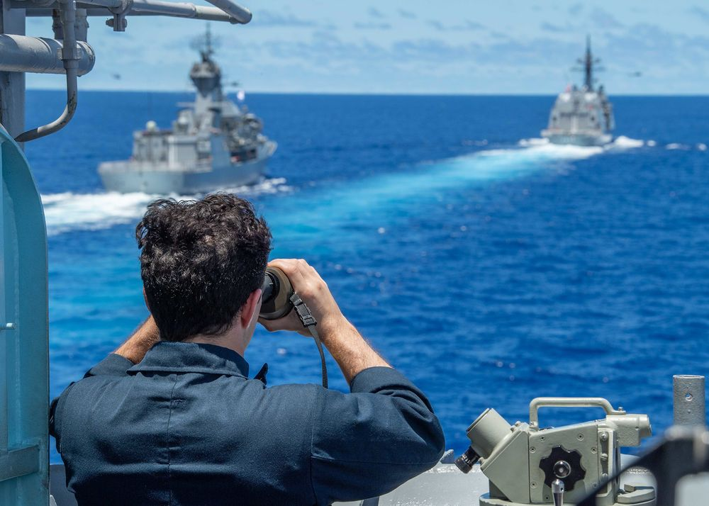 A U.S. sailor views a Royal Australian Navy vessel and a Japan Maritime Self-Defense Force vessel in the South China Sea on July 21.
