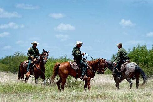 U.S. Border Patrol agents work on horseback in a field near Carrizzo Springs, Texas on July 3