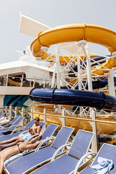 """Sunbathing in the Pool and Sports Zone. This """"neighborhood"""" stretches the length of the ship with four types of pools, two surf simulators, a zip line, and views of the Boardwalk and Central Park neighborhoods below."""