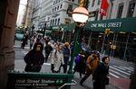 Pedestrians walk along Broadway near the New York Stock Exchange.
