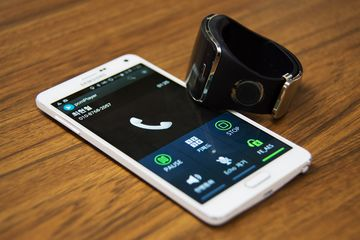 The prototype of TipTalk device, developed by Innomdle Lab, sits on a Samsung Electronics Co. Galaxy Note 4 smartphone displaying the TipTalk app in this arranged photograph taken in Seoul, South Korea, on Friday, Oct. 23, 2015. Choi, a Samsung Electronics engineer, developed a wristband that keeps eavesdroppers from listening to smartphone conversations. Photographer: SeongJoon Cho/Bloomberg