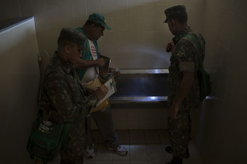 A municipal employee working on a Dengue and Zika prevention campaign and two soldiers from the Brazilian army, inspect a bathroom for signs of mosquitoes in Olinda, Brazil.