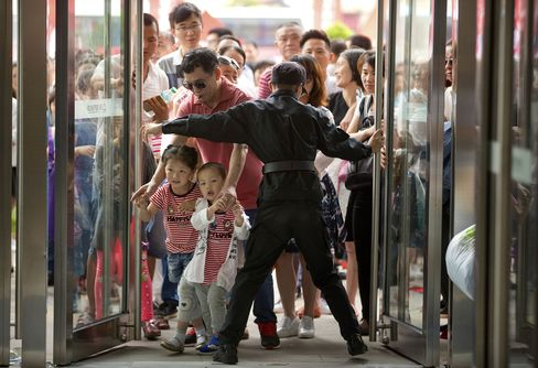 A security guard opens the entrance doors for the grand opening of the Wanda Mall at the Wanda Cultural Tourism City on Saturday.