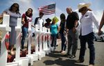 Volunteers pray over white handmade crosses memorializing the victims of a mass shooting which left at least 22 people dead on August 5, 2019 in El Paso, Texas.