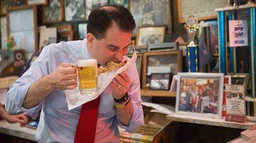 Republican presidential hopeful wisconsin governor scott walker washes down a 'cheezborger' with schlitz beer at the famed billy goat tavern during campaign stop on july 27, 2015 in chicago, illinois.