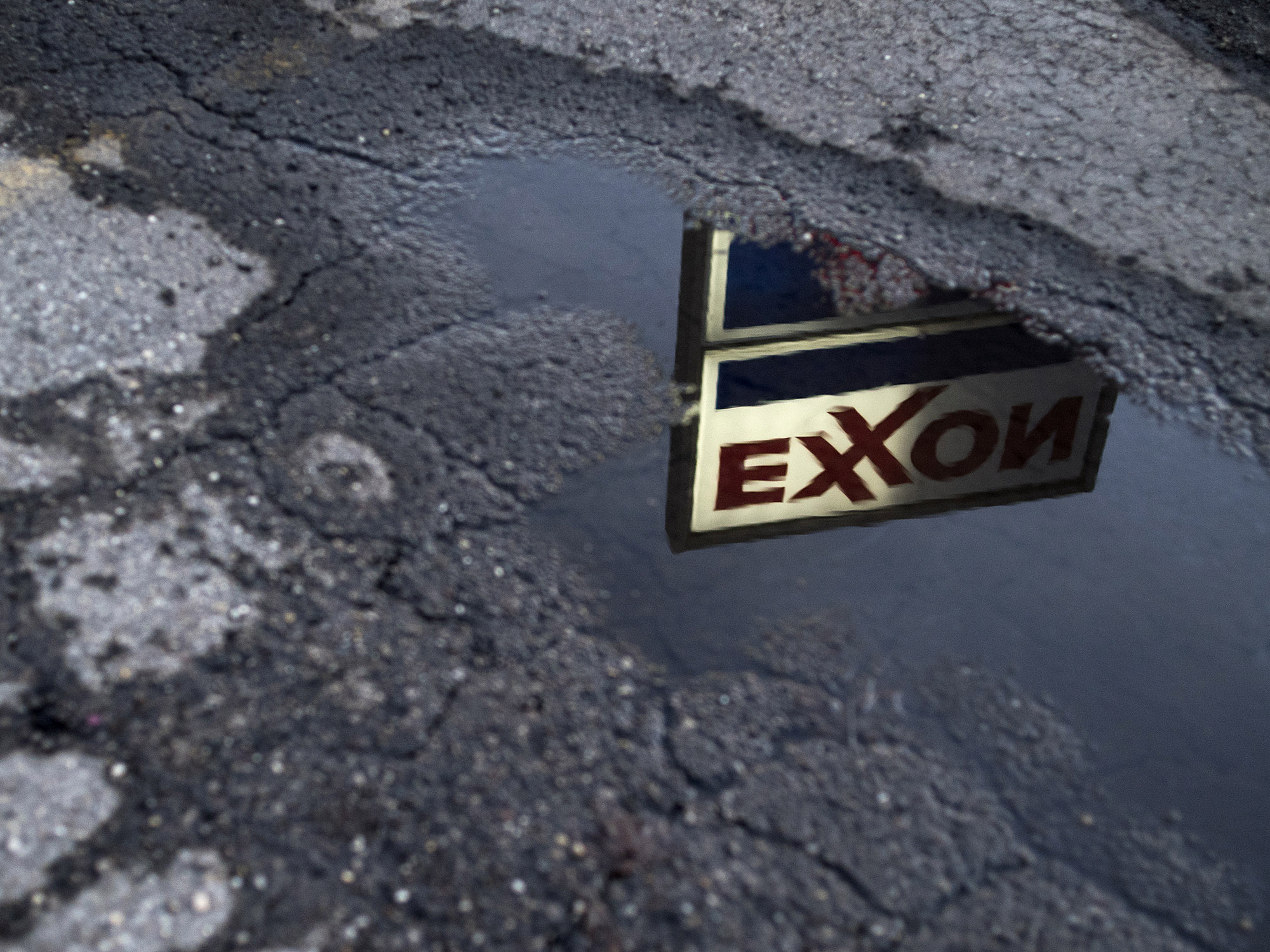 Exxon Mobil Corp. signage is reflected in a puddle at a gas station in Nashport, Ohio.