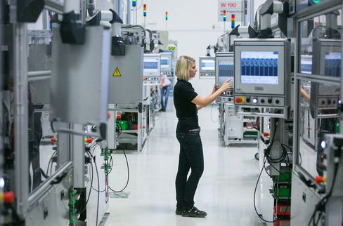 An employee uses a touchscreen panel on the automobile gasoline direct injector valve assembly line at the Robert Bosch plant in Blaichach, Germany, on March 31.
