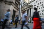 Pedestrians walk along Wall Street near the New York Stock Exchange (NYSE) in New York, U.S..