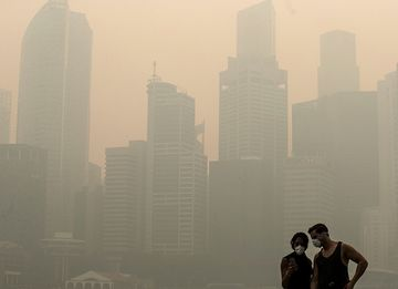 Pedestrians look at a smart device in the Marina Bay district as buildings in the central business district stand shrouded in smog in Singapore.