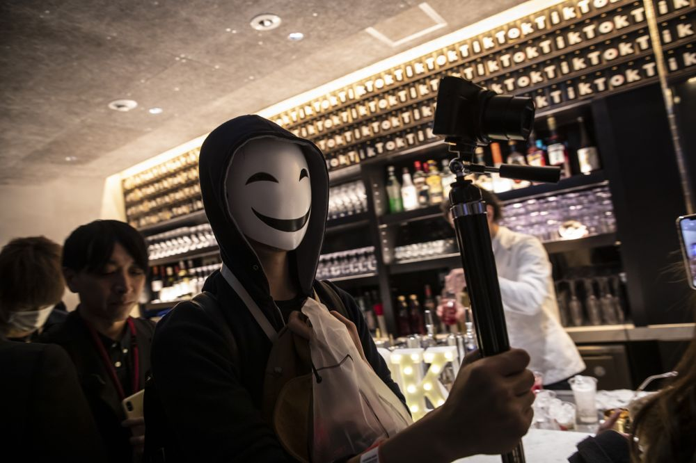 An attendee wearing a mask carries a camera during the TikTok Creator's Lab 2019 event hosted by Bytedancein Tokyo.