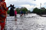 People wade across a submerged road following flash flooding in the semi-arid northern town of Isiolo, Kenya