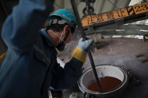 An employee cleans residue from a container at an aluminum smelting facility in Zouping, China.