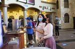 People wearing protective masks stand at a concessions counter at a Regal Cinemas theater in Austin, Texas, U.S., on Friday, Aug. 21, 2020.