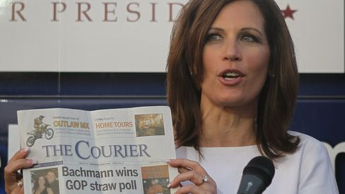 Michele Bachmann holds up a copy of the local paper as she speaks at the Black Hawk County GOP Lincoln Day Dinner on Aug. 14, 2011, in Waterloo, Iowa, after her victory at the Iowa Straw Poll.