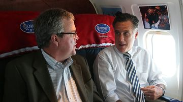 Republican presidential nominee Mitt Romney, right, talks with former Florida Governor Jeb Bush aboard his campaign plane on Oct. 31, 2012.