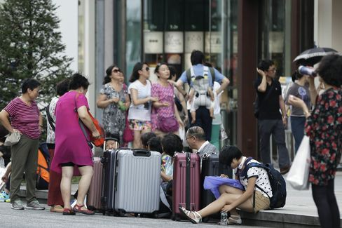 A group of Chinese tourists sit with their suitcases in the Ginza district of Tokyo.