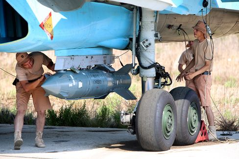 Russian military support crew attach a satellite guided bomb to SU-34 jet fighter at Hmeimim airbase in Syria on Oct. 3, 2015.