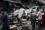A woman uses a smartphone, center, as workers move boxes at a street market in Chongqing.