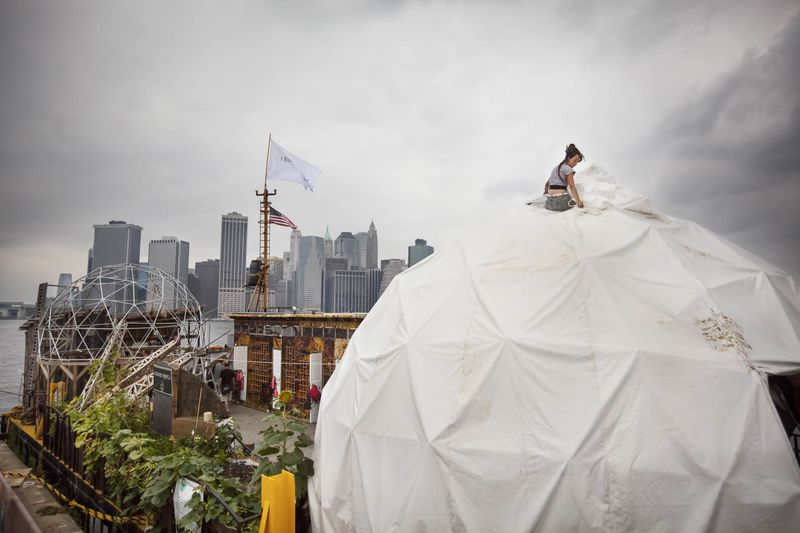 © 2009 MICHAEL NAGLE -- +1-917-202-8764 -- NOT TO BE PUBLISHED WITHOUT PERMISSION. BROOKLYN -- AUGUST 09, 2009: Mayra Cimet climbs a dome on the Waterpod, docked along the waterfront at Joralemon Street, to reattach a piece of tarp on August 09, 2009 in Brooklyn. (PHOTOGRAPH BY MICHAEL NAGLE)