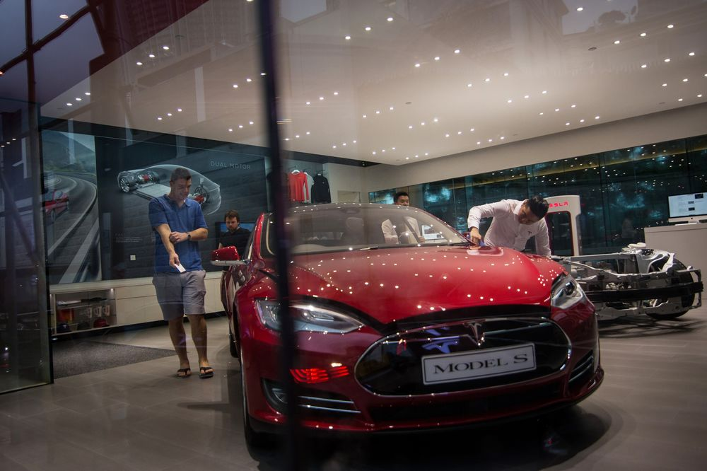 Customers look at a Tesla Motors Inc. Model S electric vehicle at the company's showroom in Hong Kong.