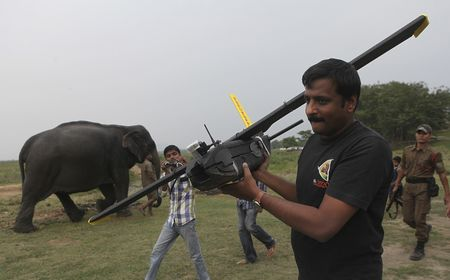 A mahout walks past with an elephant used for tourist rides as a World Wide Fund for Nature (WWF) official carries an unmanned aircraft or drone before flying them at the Kaziranga National Park at Kaziranga in Assam state, India.