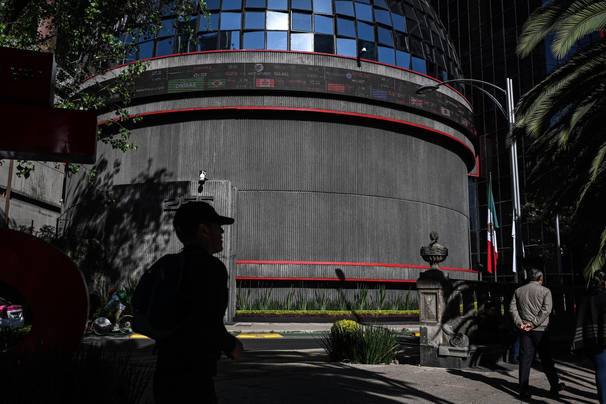 Pedestrians pass in front of the Bolsa Mexicana de Valores, Mexico's stock exchange, in Mexico City, Mexico.