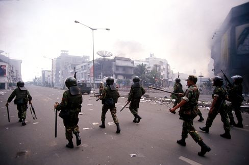 Indonesian armed forces patrol the streets during a riot in Jakarta on May 14, 1998.