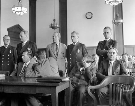 """Racketeers entered the dress industry in the bloody organizing days of the 1920s and have been connected with it ever since. One of the most notorious was Louis """"Lepke"""" Buchalter, left, who along with three other defendants, Emanuel (Mendy) Weiss (back to camera), Philip Cohen, and Louis Capone, appeared in Brooklyn County Court in New York in 1941 to answer charges arising from the murder of a trucker who wouldn't cooperate. Buchalter, who was executed for that crime, headed Murder, Inc., a gang that operated in the Garment District in the 1930s. It is estimated """"Lepke"""" and his hired killers worked dress manufacturers for a million dollars a year in tribute."""