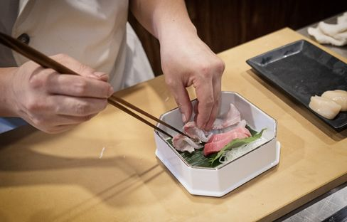 A sushi chef prepares a sashimi plate in Singapore