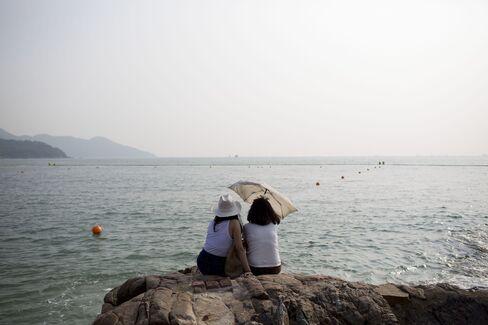 Women sit on a rock at Hung Shing Ye beach on Lamma Island in Hong Kong.