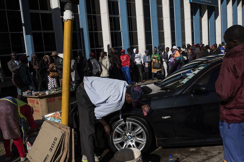 People queue outside a bankin Harare, Zimbabwe.