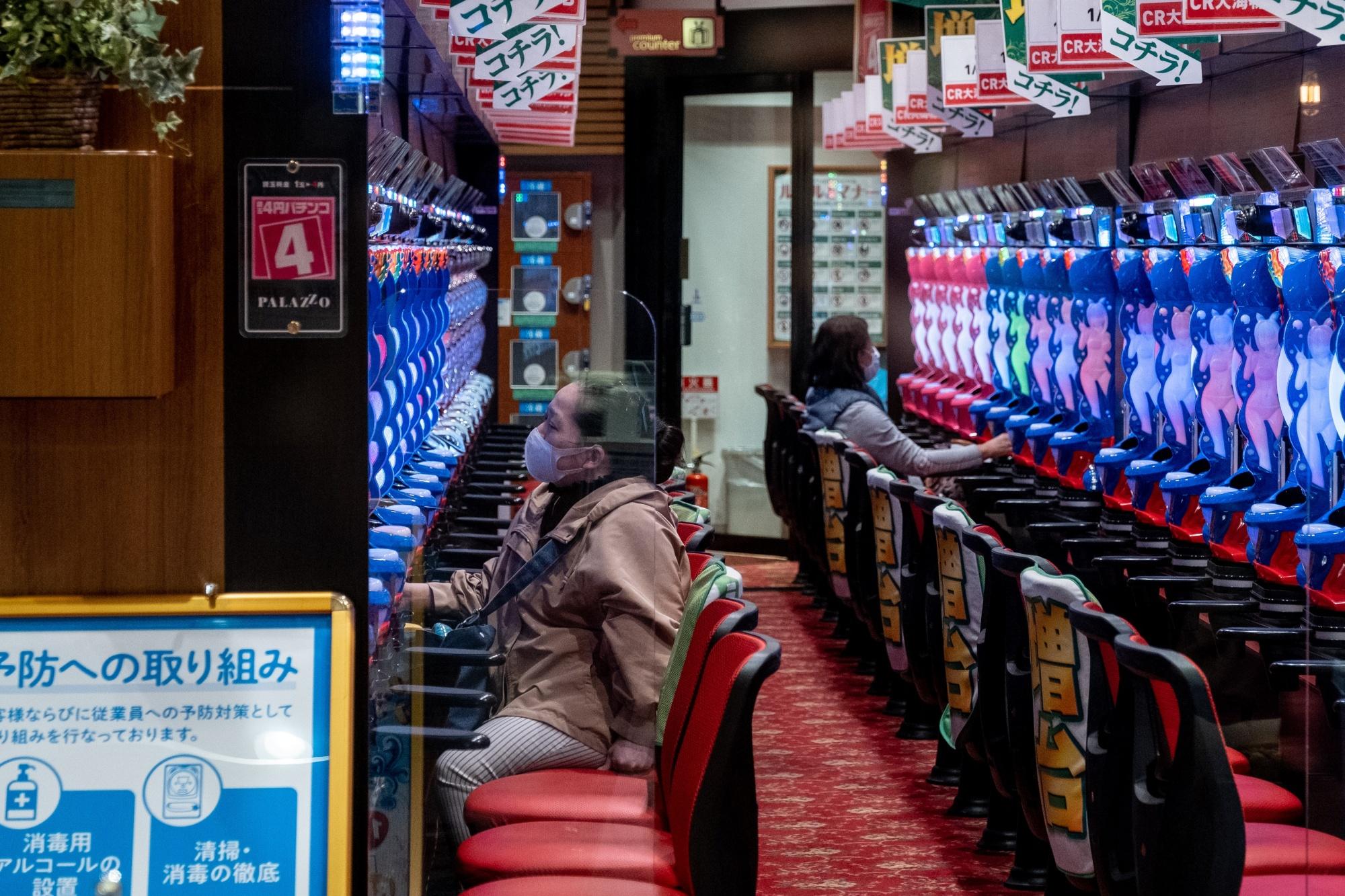 Wanita bertopeng bermain pachinko di Tokyo parloour pada 5 April.