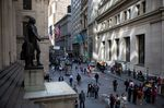 Pedestrians walk along Wall Street near the New York Stock Exchange.