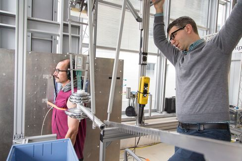 Roland Behrens, a research manager, right, prepares a mechanical pendulum for pain threshold tests at the robot collision testing facility in the Fraunhofer Institute in Magdeburg, Germany.