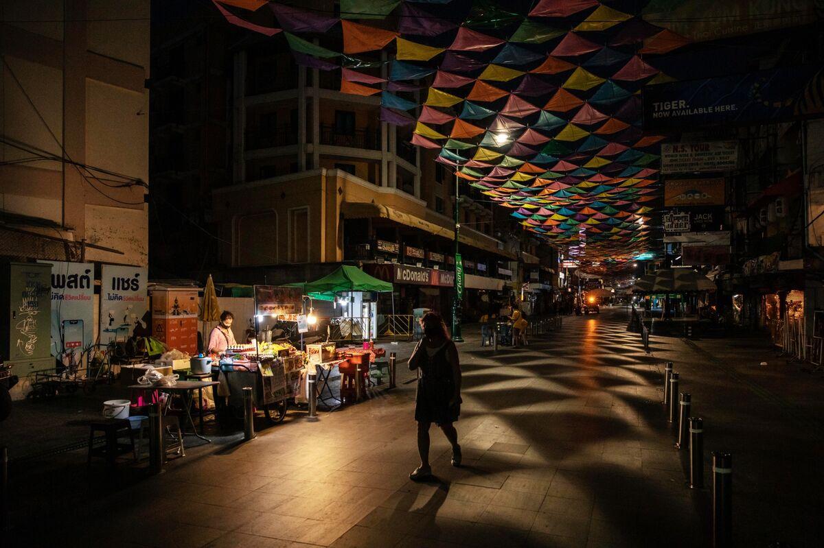 A pedestrian passes a food vendor at a deserted Khaosan Road in Bangkok, Thailand.