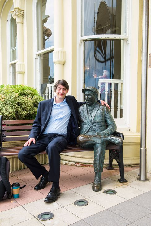 Adrian Forbes, who runs the startup TGBEX, sits next to a statue of actor Norman Wisdom, who retired to the island.