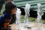 A girl plays at a water fountain in Sing