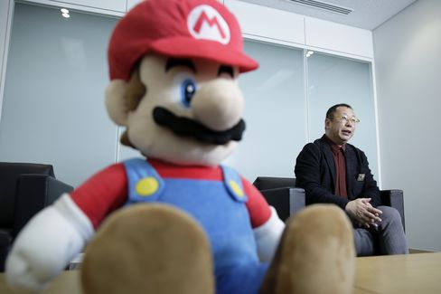 Takashi Tezuka, producer at Nintendo, speaks while a Mario doll sits displayed during an interview at the company's development center in Kyoto.