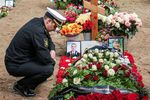 A Russian Navy officer pays his respects by a grave during a funeral of the 14 Russian Navy officersat the Serafimovskoye cemetery.